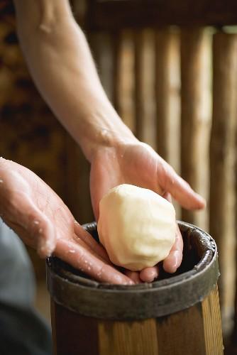Hands holding a ball of butter over a butter churn