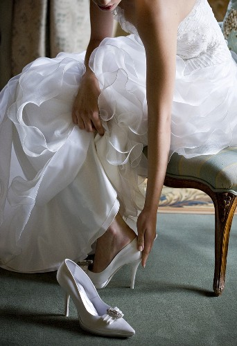 A bride taking off her shoes