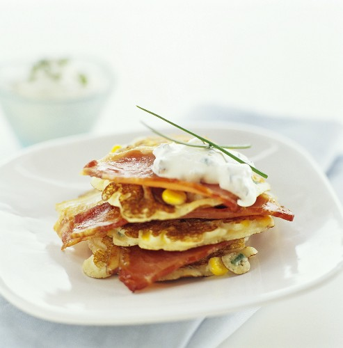Corn pancakes and bacon with sour cream