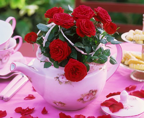 Red roses in teapot on tea table
