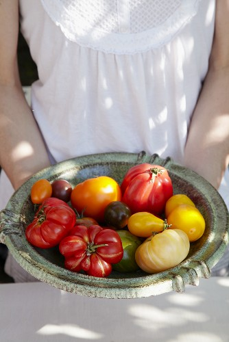 Woman holding a dish of different kinds of tomatoes