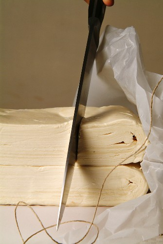 Fresh puff pastry being cut with a knife