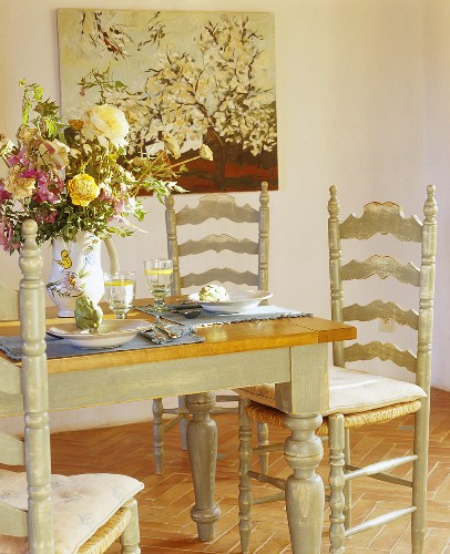Laid table with jug of flowers and artichokes