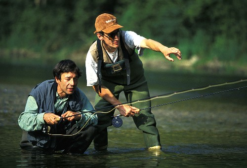 Two men fly fishing in a river (France)