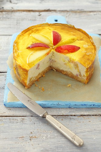 Cheesecake topped with pears, peaches and jelly, pieces removed