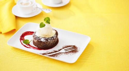 Warm chocolate pudding with ice cream and raspberry sauce