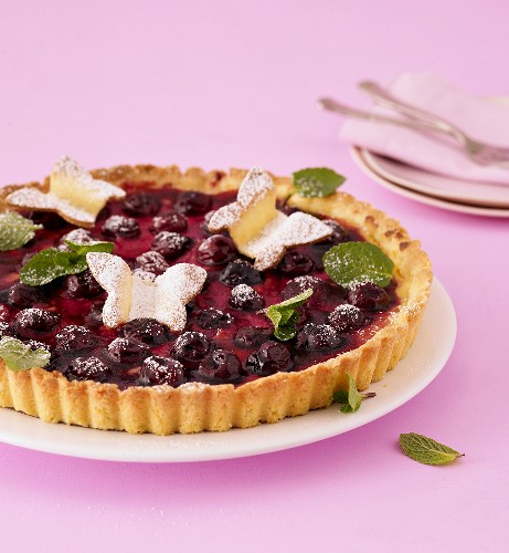 Marzipan cream tart with cherries and pastry butterflies