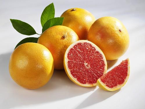 Mehrere rosa Grapefruits (ganz, halbiert und Schnitz)