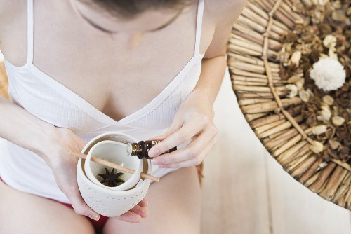 A woman drizzling scented oil in an oil burner