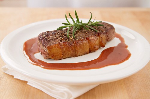 A steak with rosemary and gravy