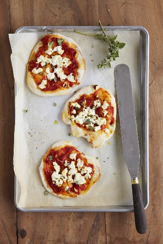 Small tomato and ricotta pizzas with oregano on baking tray