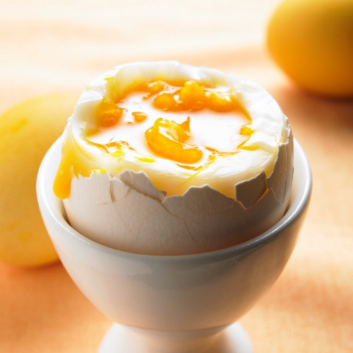 A soft boiled egg in an eggcup (close up)