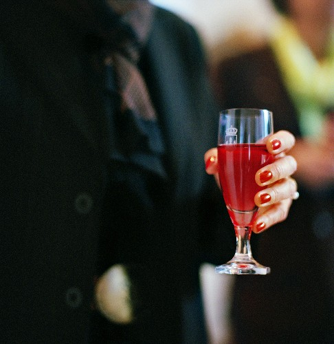 Woman's hand holding a glass of Kir Royal
