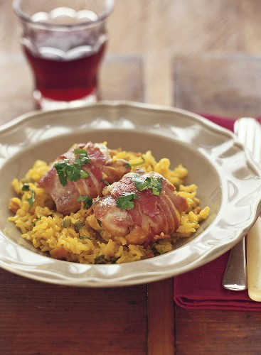 Chicken thighs wrapped in bacon on saffron rice