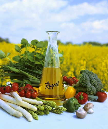 Rape seed oil with fresh vegetables in front of rape field
