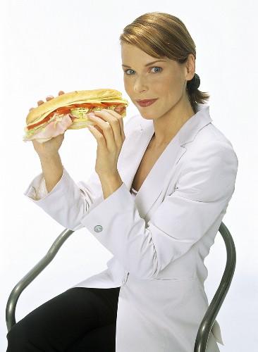 Junge Frau hält ein Sandwich in den Händen
