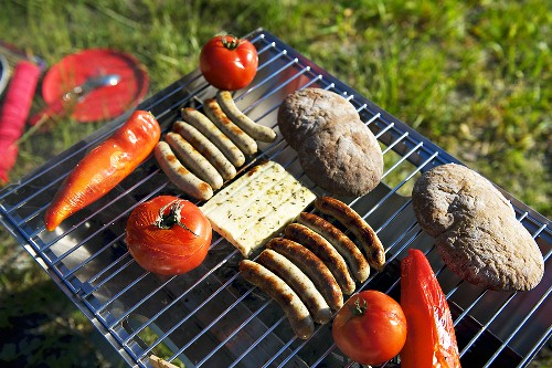 Sausages, cheese and vegetables on a barbeque