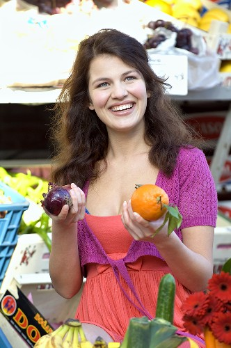 Young woman shopping, holding an onion and an orange