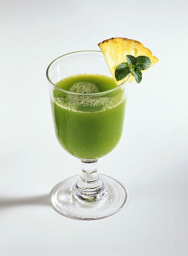 A glass of wheatgrass drink with pineapple