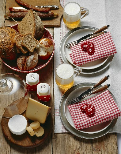 Table laid for hearty snack of cheese, bread, sausage & beer