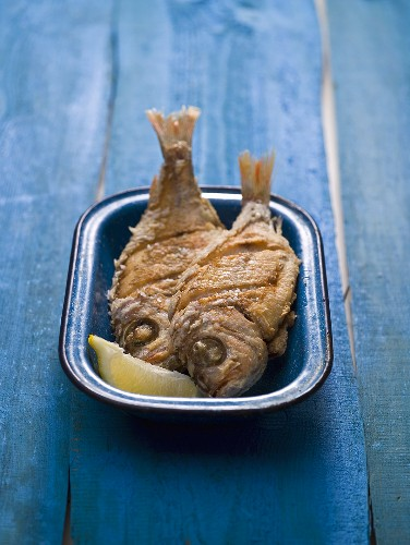 Two fried snappers in an enamel dish