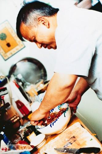 Asian man preparing seafood dish