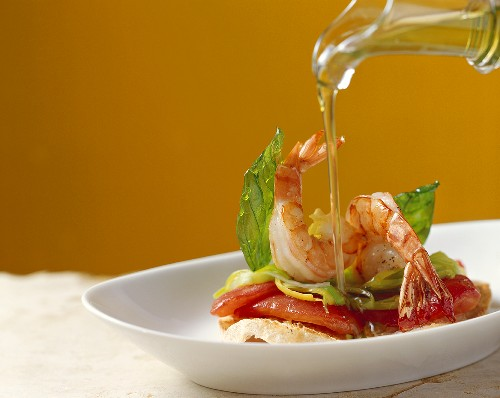 Drizzling prawns on ciabatta with olive oil
