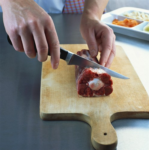 Separating the joints of an oxtail with a knife