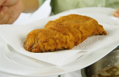Draining Wiener schnitzel (breaded veal escalope) on kitchen roll