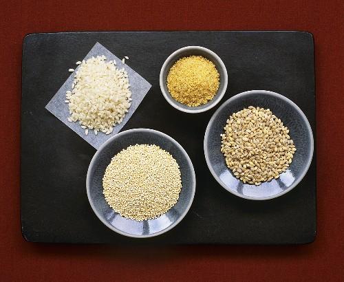 Pearl barley, quinoa, risotto rice and bulgur on plates