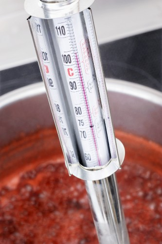 Testing the temperature of jam with a jam thermometer