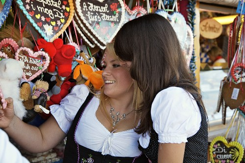 Two young women in traditional Bavarian dress at sweet stall