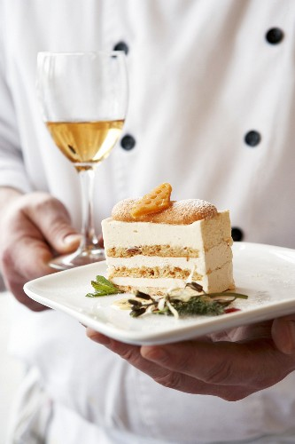 Chef carrying a piece of cream cake on a plate & dessert wine