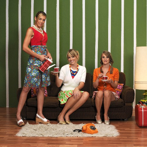 Three young women having coffee in living room