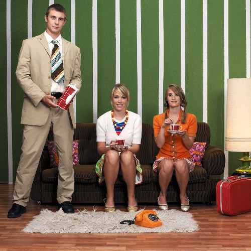 Two women and one man having coffee in living room