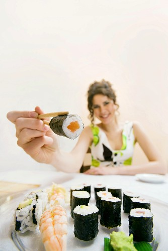 Young woman offering sushi