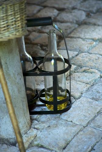 Wine bottles in carrier on stone floor (Château de la Verrerie, France)