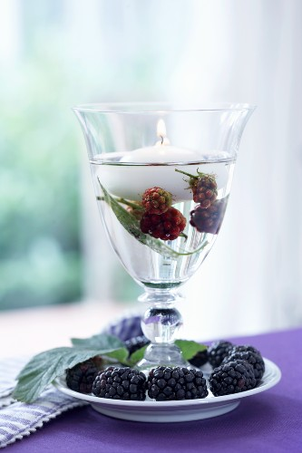 A wine glass being used as a lantern with blackberries