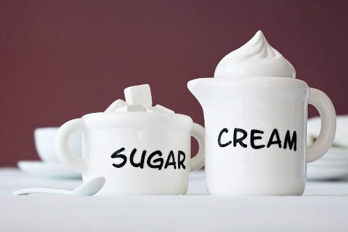 A cream jug and a sugar pot with writing