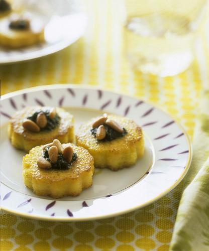Bocconcini di polenta (Polenta rounds with pesto & pine nuts)