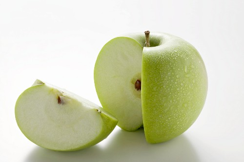A 'Granny Smith' apple with a quarter cut out