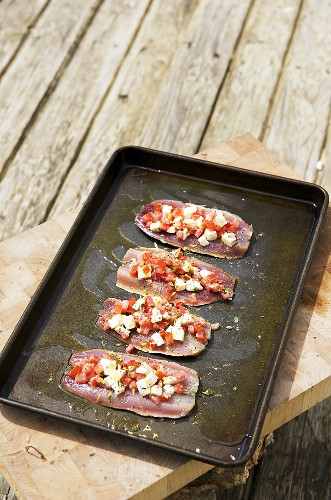 Sardines with cheese and tomato stuffing on a baking tray
