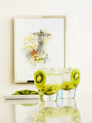 Kiwi fruit drinks on marble slab in front of picture (Brazil)
