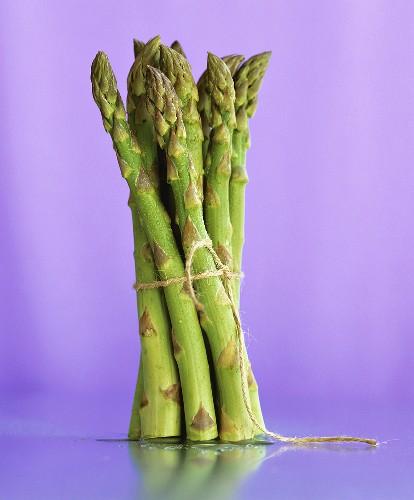 A bundle of green asparagus against a purple background