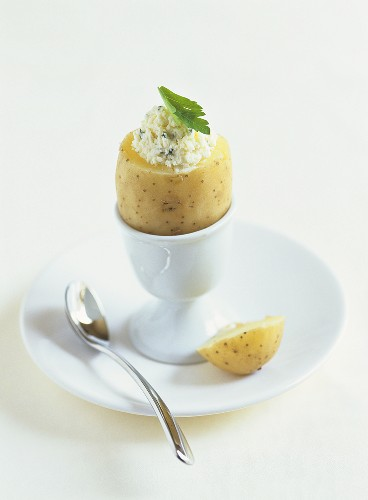 Boiled potato with cottage cheese and herbs in eggcup