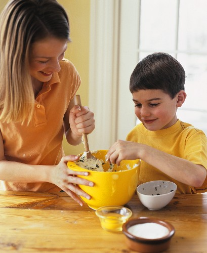 Girl and boy mixing ricotta with herbs