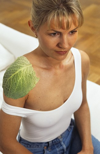 Young woman with cabbage compress on her shoulder