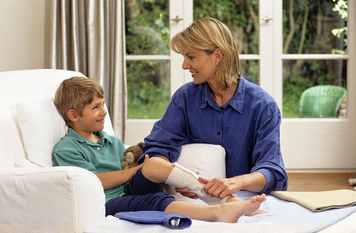Mother putting a compress on her son's leg