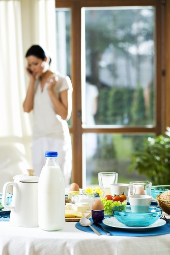 Breakfast table, woman on mobile phone in the background