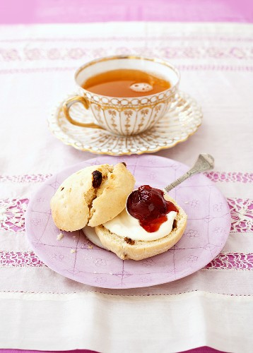 Scone with cream and jam and a cup of orange tea
